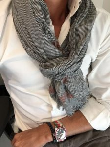 button down shirt and plaid scarf tied around the neck