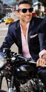 men's navy suit with pink button down shirt unbuttoned and cuffed on a motorcycle