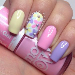 spring nail polish designs, yellow, pink, purple with one white floral nail, spring nail art