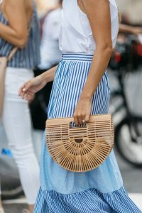 white ruffled top, blue and white striped maxi skirt and wooden clutch