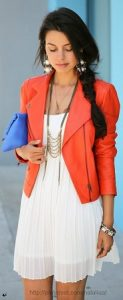 women's white pleated dress with orange leather bomber and statement necklace earrings